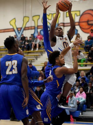 North Side's Jerry Robertson goes up for a shot over an host of McNairy County County defenders during their game, Tuesday, Jan. 30. North Side defeated McNairy Central 77-59.