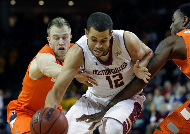 Boston College forward Ryan Anderson (12) attempts to drive through the defense of Syracuse forward Rakeem Christmas, right, and Syracuse guard Trevor Cooney (10) during the first half of their NCAA college basketball game at Boston College in Boston, Monday, Jan. 13, 2014.