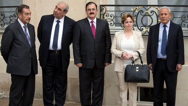 Members of the Syria National Coalition, from left, Farouk Tayfour, Michel Kilo, Salem Idriss, Suheir Atassi, and Burhan Ghalioun wait for the meeting of France's president Francois Hollande and Syria National Coallition president Ahmed al-Jarba at the Elysee Palace in Paris, France, July 24, 2013.