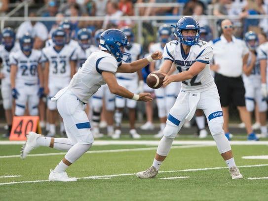 Barron Collier quarterback Jacob Kuhlman hands the