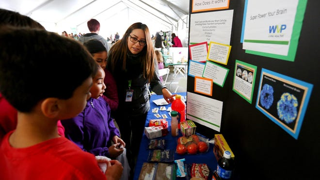 Elena Piceno speaks to students from Auburn Elementary about what foods are healthy for them at the WPV: Superpower Your Brain booth during Urban AgFest Oct. 22 at Parrish Middle School.