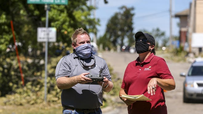 Field property specialist Sam Ellenburg, left, and property large loss claims manager Vicky Walters of Grange/Integrity Insurance talk while a drone flies what they refer to as a lawnmower grid Aug. 19 taking damage photos for an insurance claim in Cedar Rapids, Iowa.