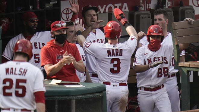 Los Angeles Angels' Taylor Ward, center, is greeted by teammates after he scored on a single hit by Justin Upton during the eighth inning of a baseball game against the Houston Astros, Sunday, Sept. 6, 2020, in Anaheim, Calif.