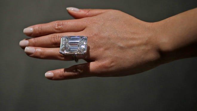 A Sotheby's employee models a 100-carat emerald-cut diamond.