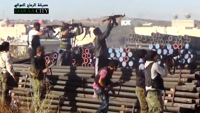 Syrian opposition fighters fire at government forces near Daraa customs in Daraa al-Balad, Syria.