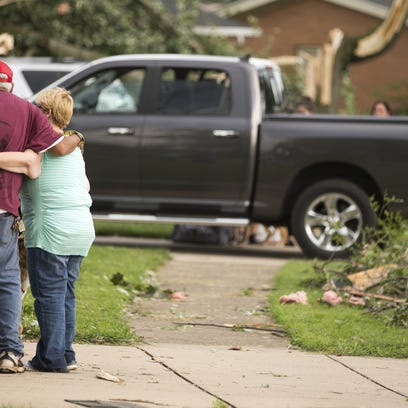 A couple hugs amid damage after a tornado that touched