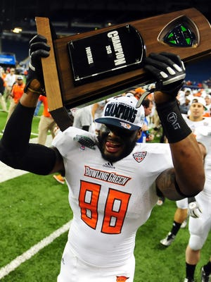 Bowling Green defensive lineman Kendall Montgomery celebrates with the trophy after the Falcons defeated the Northern Illinois Huskies 47-27 to win the MAC Championship.