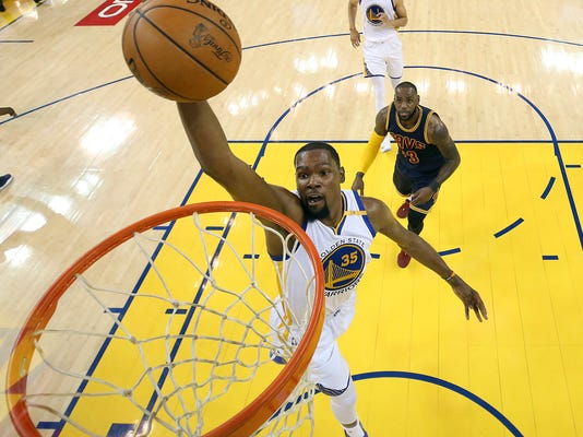 FILE - In this June 1, 2017, file pool photo, Golden State Warriors forward Kevin Durant (35) dunks in front of Cleveland Cavaliers forward LeBron James during the first half of Game 1 of basketball's NBA Finals in Oakland, Calif. Beginning his 11th NBA season at age 29 and fresh off his first career championship, Durant is as determined as ever.  (Ezra Shaw/Pool Photo via AP, File)