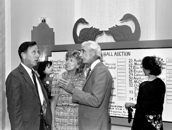 John Warner, front left, Peggy Warner and Marvin Runyon chat in front of the Swan Ball auction preview party board while Jamie Granbery, back left, and Renee Mathews post some bids May 23, 1984. The party took place at the new Vanderbilt Plaza Hotel.