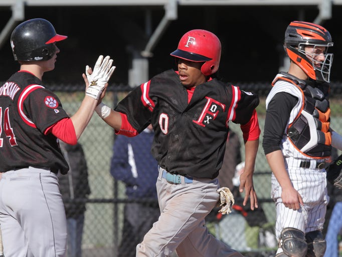 Fox Lane's Dion Austrie, center, celebrates with Andrew Workman, left, after scoring in the first inning during a baseball game against Mamaroneck April 10, 2014, in Mamaroneck. ( Matthew Brown / The Journal News )