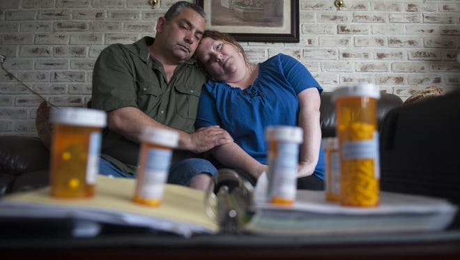 Jennifer Crispaldi and her husband, John, sit by some of Jennifer's medications and medical records in their Blackwood home.  Jennifer has suffered with a disorder called dysautonomia since she was 21. Doctors didn't identify the problem for 16 years. The neurological disorder interferes with multiple systems. Symptoms include frequent fainting spells, low blood pressure and digestive problems.