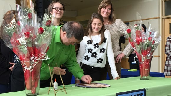 Gates Orlando, left, helps decorate a floral image of Paul Guyette at a ceremony for families touched by organ donation at Strong Memorial Hospital. Guyette died suddenly and his heart was donated to Orlando. Guyette's daughters, Jenna and Emma, and his widow, Mary, look on.