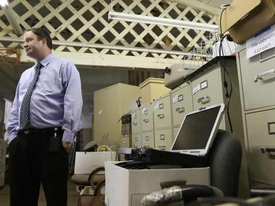 City Comptroller and Treasurer Corey Ladick stands near a box of Pansonic Toughbook laptops for sale at the surplus sale happening this Sunday, while touring the supplies August 10, 2016.