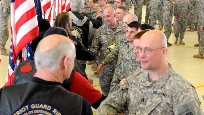 Members of the Patriot Guard Riders shake hands with soldiers of C Company 1-171 after a deployment ceremony.