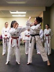 "Darci Miranti practices self-defense techniques with Louise Lluisma, 14, during class at Big Sky Taekwondo. Miranti's goal ""is to be a good leader and role model for the girls. Girls don't always get good role models in activities they're taking part in."""