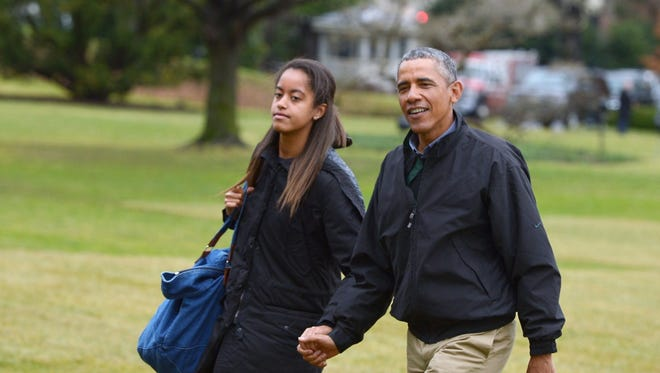 In this January 4, 2015 file photo, US President Barack Obama (R) and daughter Malia walk across the South Lawn upon return to the White House in Washington, DC.