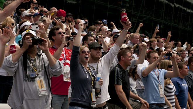Fans cheer in the final moments of the race Sunday, May 26, 2013, during the 97th running of the Indianapolis 500, at the Indianapolis Motor Speedway.