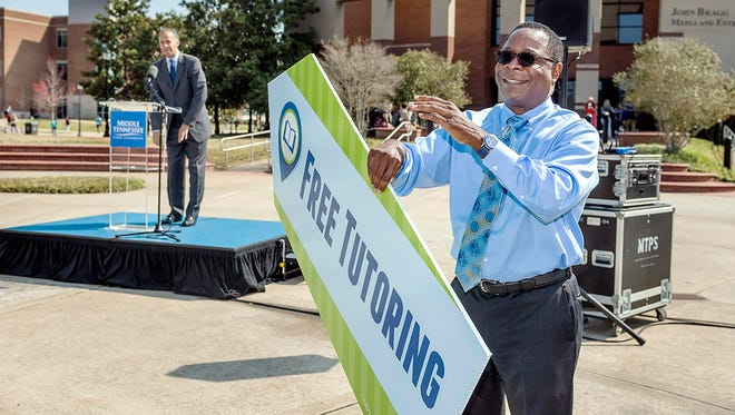 """MTSU President Sidney A. McPhee flips a free tutoring sign as Vincent Windrow, vice provost for Student Success, revs up the crowd attending the """"MT Flips Over Tutoring"""" event March 21 outside the James E. Walker Library."""