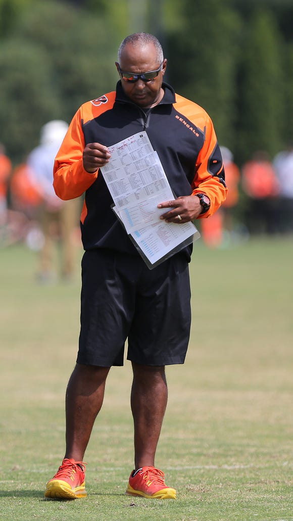 Coach Marvin Lewis reads play sheets during Cincinnati Bengals training camp on the practice fields at Paul Brown Stadium.