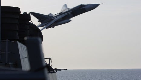 A Russian Sukhoi Su-24 attack aircraft makes a very low altitude pass by the USS Donald Cook  on April 12, 2016 in the Baltic Sea.