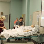 "First-semester nursing students Kayla Breland of Carriere, left, and Kristi Guarino of Necaise prepare ""Missy Duncan"" for hip replacement surgery using a simulation lab purchased with a grant from the Lower Pearl River Valley Foundation."