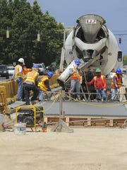 In this April 2013 file photo, Core Tech International employees install a section of rigid pavement on Marine Corps Drive as part of the bridge replacement project. The project, entirely funded by the military, is in connection with the pending military buildup.