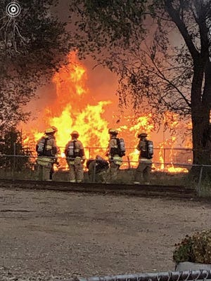 Two Pueblo firefighters walk down Bellevue Place as a fire burns behind them at an abandoned home.