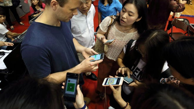 "This file photo taken on May 29, 2016 shows a foreign participant adding friends into an app on his smartphone during a matchmaking event in Hangzhou, eastern China's Zhejiang province.  The global smartphone market is sputtering in 2016, with Apple likely to see its first ""down"" year for the iPhone, a research report said June 1, 2016. Research firm IDC said worldwide smartphone sales will likely increase just 3.1 percent to 1.48 billion units, after 10.5 percent growth last year. IDC said it expects ""low single digit growth"" in the United States, Western Europe, and China while Japan and Canada are expected to contract by 6.4 percent and 6.9 percent, respectively.  / AFP PHOTO / STRSTR/AFP/Getty Images ORIG FILE ID: 552485021"