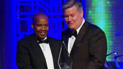 Eric Biribuze, left, a Corning Inc. engineer, is joined by Executive Vice President Marty Curran as he receives an award at a national STEM conference.