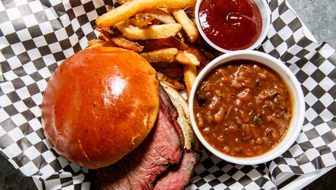 Hoggin' It BBQ in Okauchee serves a tasty sliced brisket sandwich with fries and baked beans. Thursday, July 28, 2017.