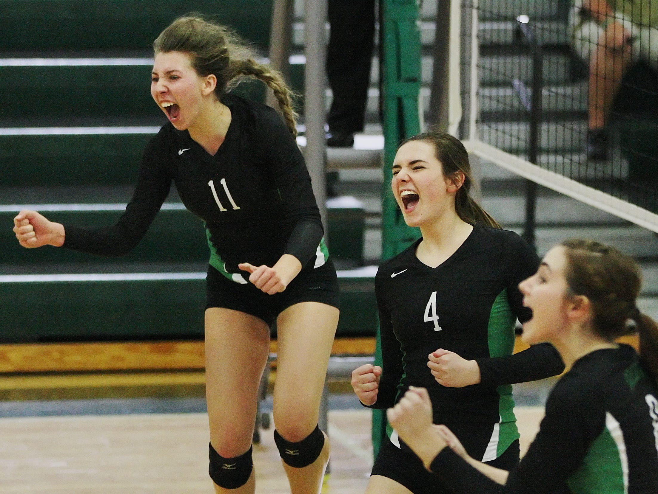 Fort Myers High School's Alayna Ryan, left, Sadie Davis, center, and Erin Gear celebrate scoring a point against Barron Collier in the Region 6A-3 semifinal volleyball game Saturday at Fort Myers High School. Fort Myers beat Barron Collier 3-0.
