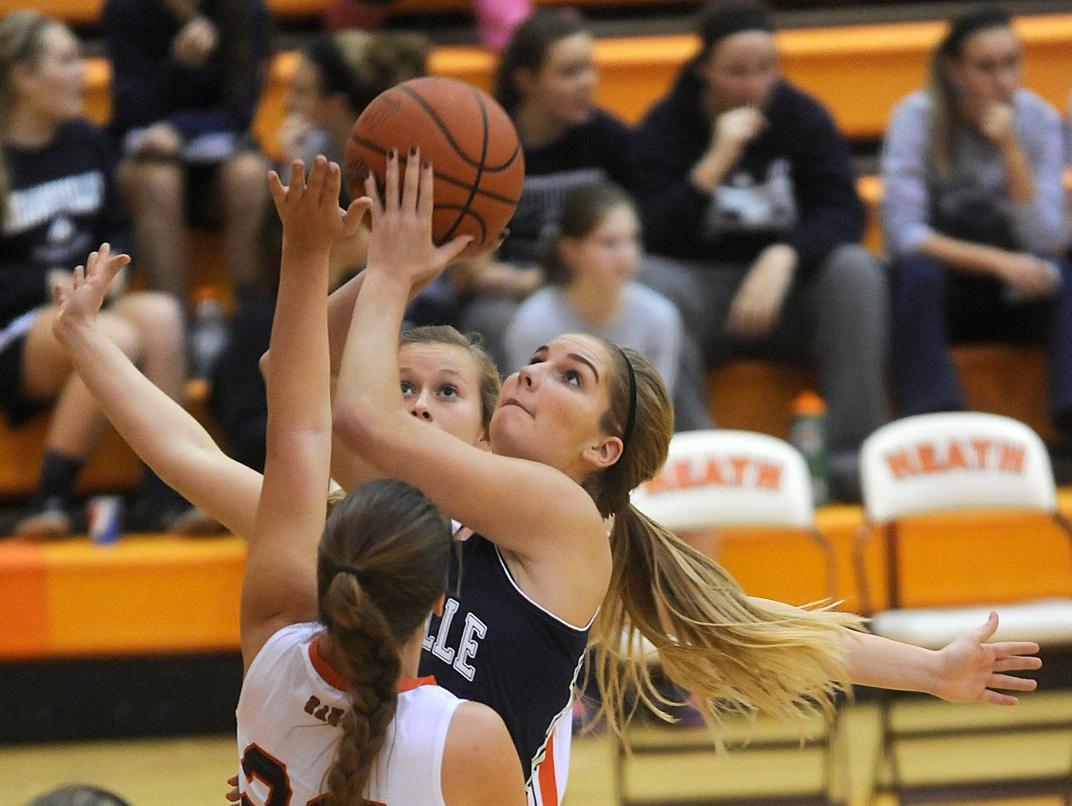 Granville's Courtney Brooks takes a shot against defense from Heath's Madi Shoemaker on Tuesday. The Blue Aces defeated the Bulldogs 54-43.
