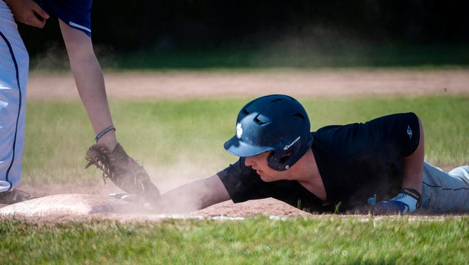 MMU's Josh Springer, right, gets back to first ahead of the tag by Milton's Andrew Harvey in Milton on Thursday, April 21, 2016.