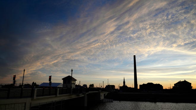 Hamilton Manufacturing Co.'s 233-foot smokestack is seen at sunset in Two Rivers on Saturday, May 30, 2015, the night before it was demolished. It towered over the Two Rivers landscape for more than 100 years.