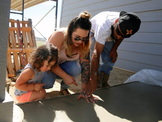 Hailey Tafoya, center, puts her handprint into the