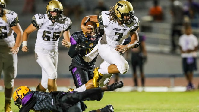 Treasure Coast's Sean Birchfield leaps over Fort Pierce Central's Jonathan Bryant during the high school football game Friday, Sept. 30, 2016, at Lawnwood Stadium in Fort Pierce. The Titans won the game in triple overtime.   CQ: Sean Birchfield, Jonathan Bryant