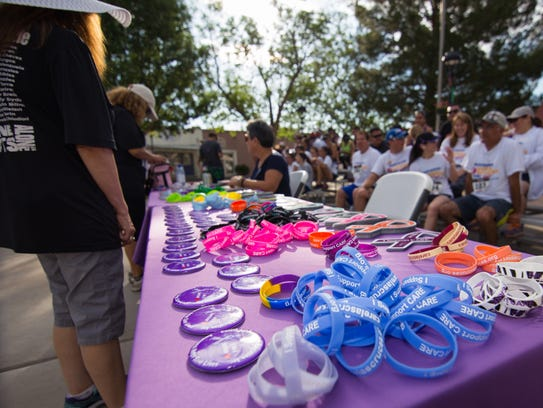 A colorful table of wristbands and buttons at the Race