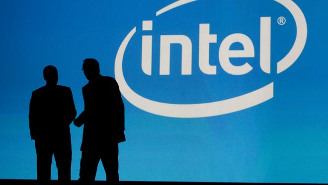 FILE - In this Jan. 7, 2010, file photo, people are silhouetted in front of the Intel sign at the International Consumer Electronics Show (CES) in Las Vegas. Microchip maker Intel is buying chip designer Altera for about $16.7 billion in cash, the company announced, Monday, June 1, 2015. (AP Photo/Laura Rauch, File)