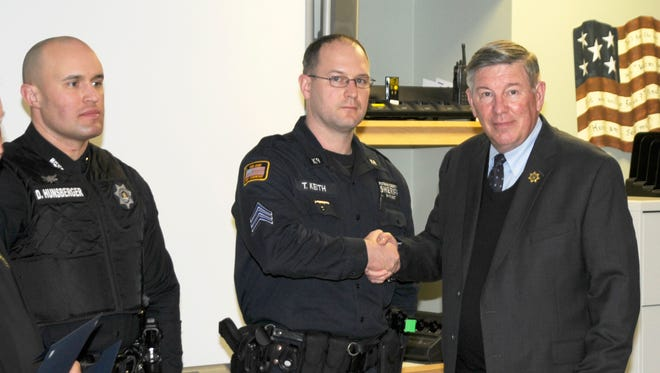 Putnam sheriff's Deputy Daniel Hunsberger, left, and Sgt. Timothy Keith, center, received commendations from Sheriff Donald Smith, right, Feb. 16 for preventing a Southeast man's suicide.