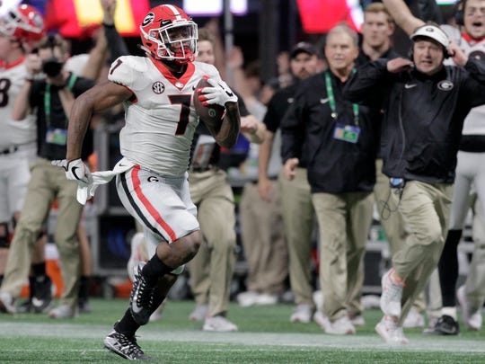 Georgia coach Kirby Smart, right, runs down the sideline as running back D'Andre Swift (7) runs for a 64-yard touchdown against Auburn in the Southeastern Conference championship NCAA college football game Saturday, Dec. 2, 2017, in Atlanta, Ga. (C.B. Schmelter/Chattanooga Times Free Press via AP)