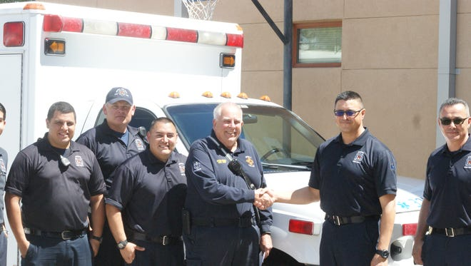 Mesilla Fire Chief Kevin Hoban, center, shakes hands with Deming Fire Chief Raul Mercado, flanked by Deming firefighters.