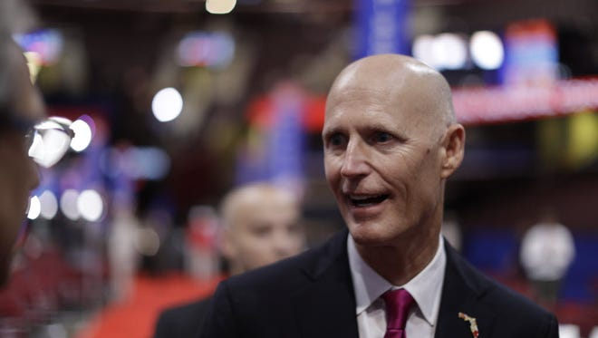 Florida Gov. Rick Scott talks to delegates as he arrives at Quicken Loans Arena before the second day of the Republican National Convention in Cleveland, Tuesday, July 19, 2016.