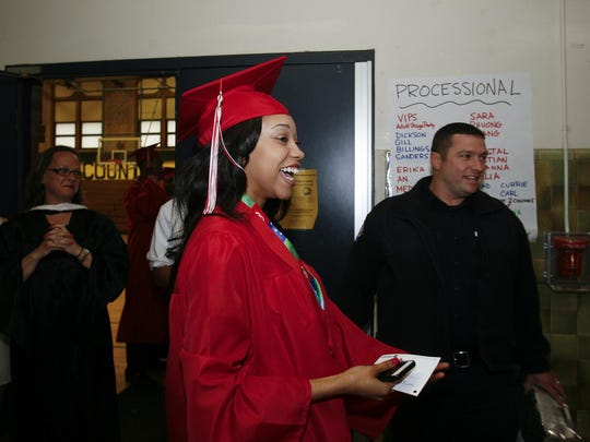 Elated Class of 2015 Sexton High School graduate Jocelyn Chapman breaks into smiles after first responders from Lansing Fire Department's Station No. 1 surprise her before her commencement walk.