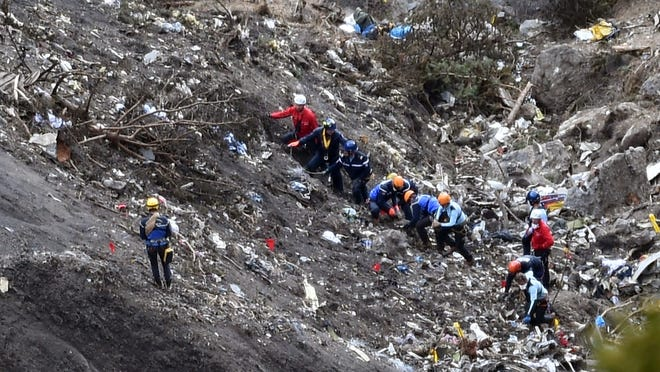 "Investigators work near scattered debris while making their way through the crash site of the Germanwings Airbus A320 that crashed in the French Alps above the southeastern town of Seyne. The young co-pilot of the doomed Germanwings flight that crashed on March 24, appears to have ""deliberately"" crashed the plane after locking his captain out of the cockpit."