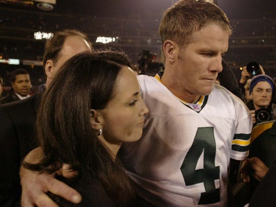 Brett Favre leaves the field with his wife, Deanna,