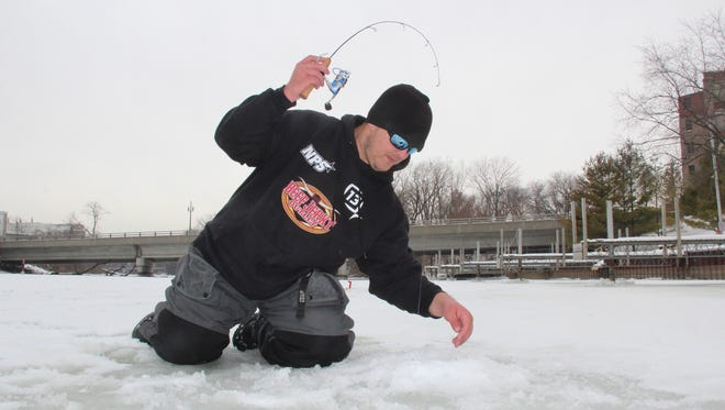 Tim Hyvonen of Oak Creek prepares to land a steelhead (or rainbow trout) while ice fishing on the Root River in Racine.