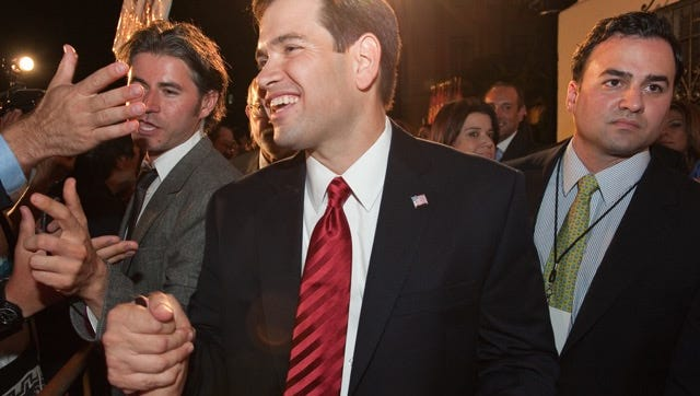 Marco Rubio exchanges handshakes with supporters while Albert Martinez (right) walks with him in 2010 in Miami after Rubio won the U.S. Senate race.