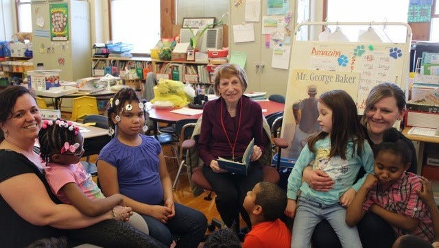 Kathy Sparacio (center), a member of the Millville Woman's Club, reads a Dr. Seuss book to first graders in Nina Crain's class at R.D. Wood School in Millville. Crain (far left) and paraprofessional Sandee Gappa (far right) also enjoyed the story.