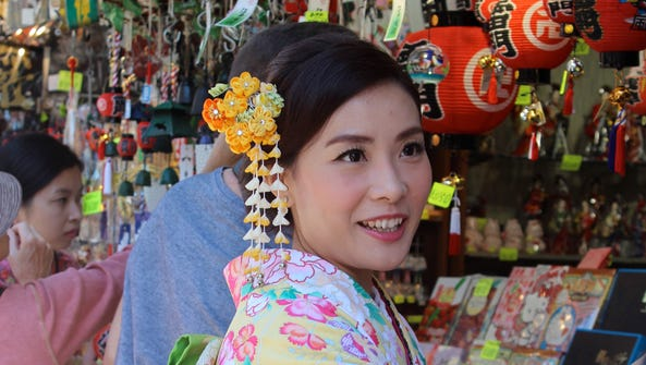 Kimono-clad woman shopping for trinkets in Kyoto market.