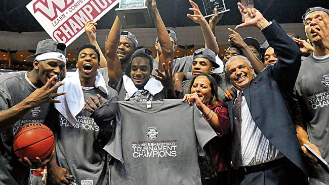 The NMSU men's basketball team celebrates after winning its fourth straight WAC Tournament championship.